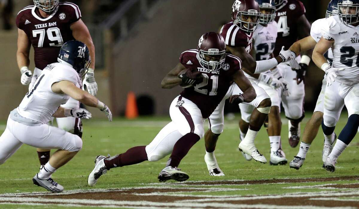 Texas A&M running back Tra Carson (21) rushes for a gain as Rice safety Garrett Fuhrman, left, pursues during the third quarter of an NCAA college football game Saturday, Sept. 13, 2014, in College Station, Texas.