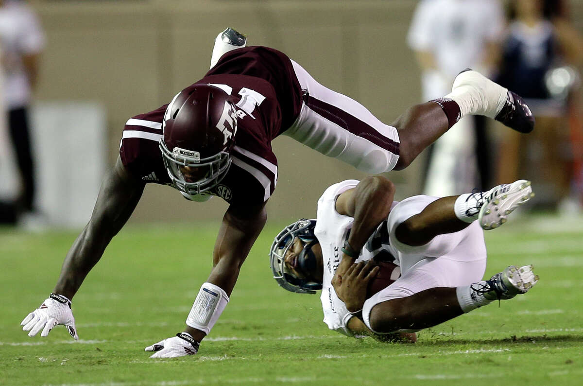 Texas A&M linebacker Donnie Baggs, top, dives over Rice running back Darik Dillard during the first quarter of an NCAA college football game Saturday, Sept. 13, 2014, in College Station, Texas.