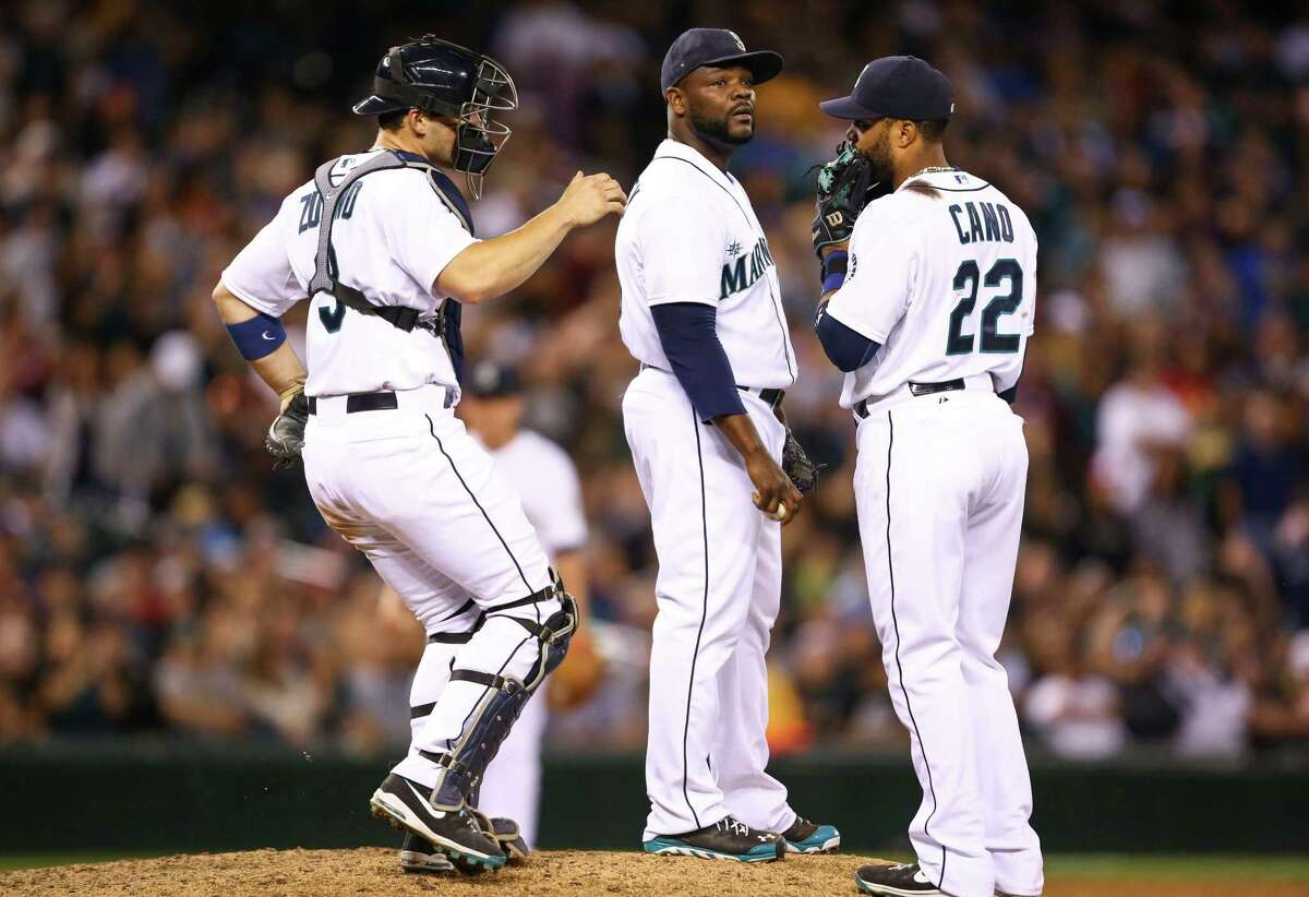 Seattle Mariners catcher Mike Zunino and second baseman Robinson Cano talk to pitcher Fernando Rodney after he walked an Oakland Athletics batter in the 10th inning as both teams compete for a wildcard spot in the playoffs. Photographed on Saturday, September 13, 2014 at Safeco Field..