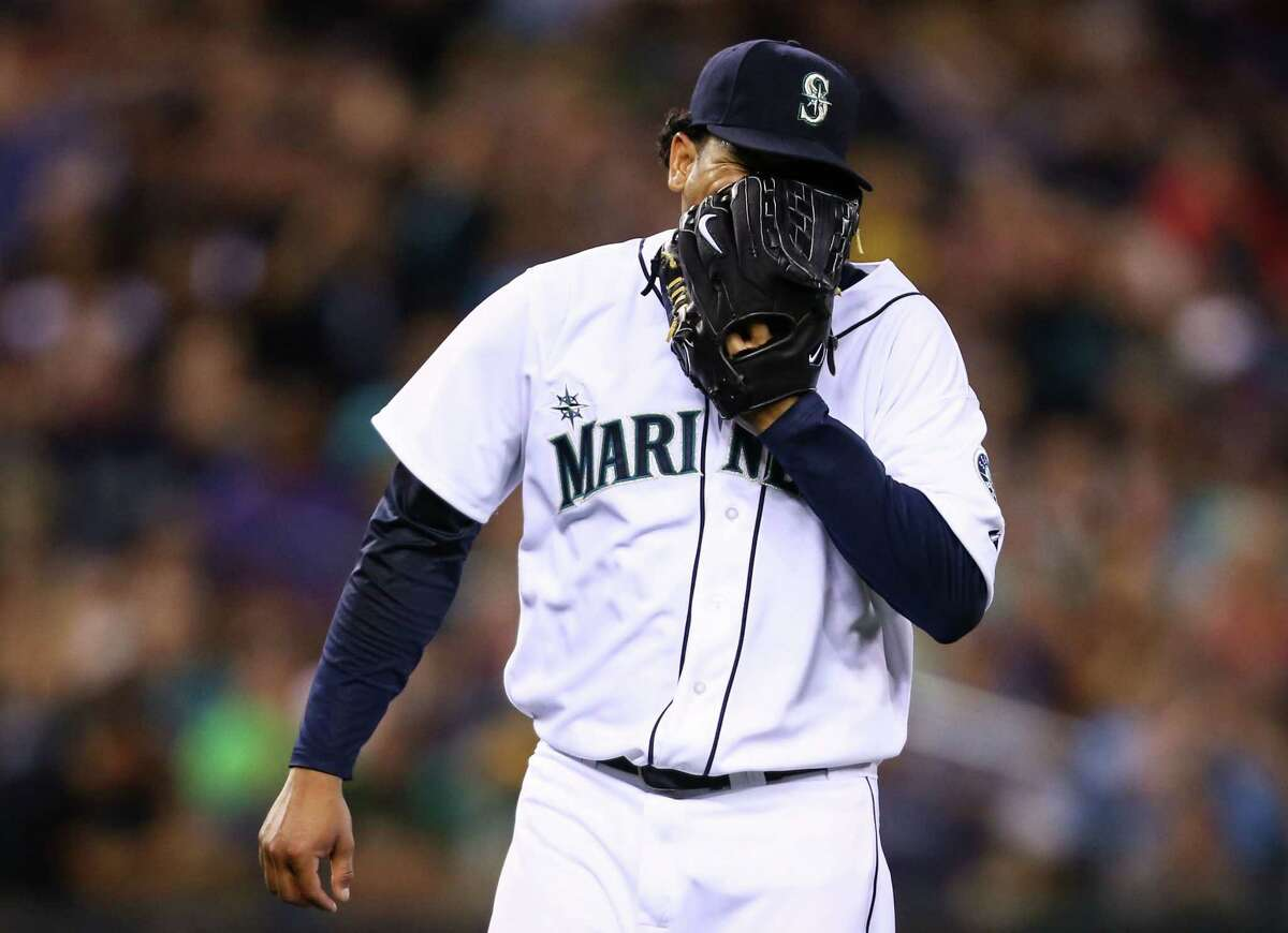 Seattle Mariners pitcher Felix Hernandez screams into his glove after an inning against the Oakland Athletics as both teams compete for a wildcard spot in the playoffs. Photographed on Saturday, September 13, 2014 at Safeco Field..