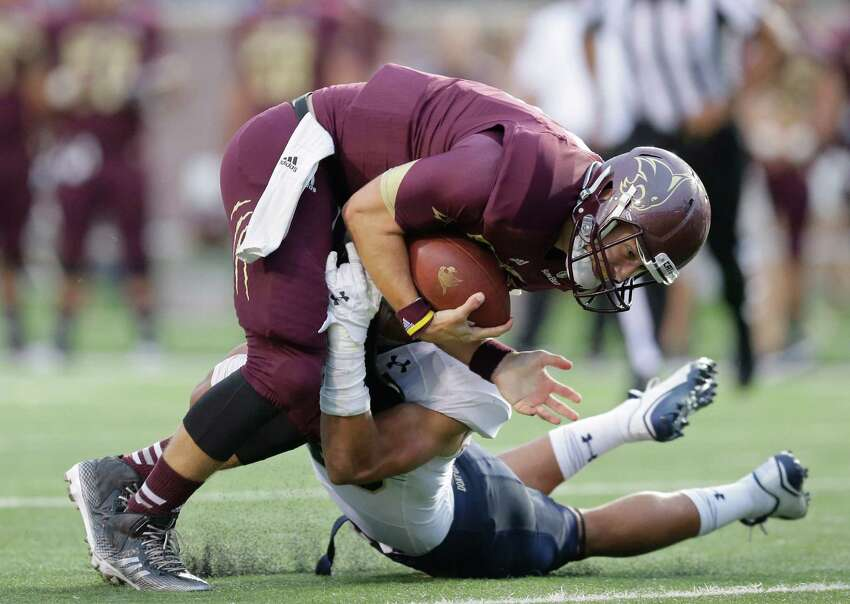 Texas State's Tyler Jones, left, is hit by Navy 's Chris Johnson, right, during the first half on an NCAA college football game, Saturday, Sept. 13, 2014, in San Marcos, Texas.