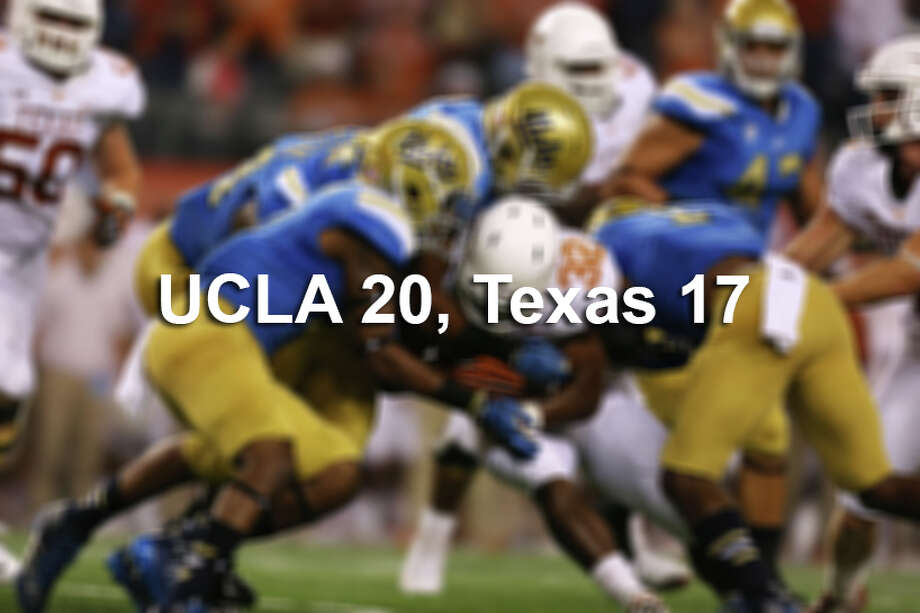 Tailback Johnathan Gray (32) gets tackled down by the UCLA defense during the UT vs. UCLA game Saturday night Sept. 13, 2014. UCLA beat Texas 20 - 17. Photo: Shelby Tauber, AP / The Daily Texan