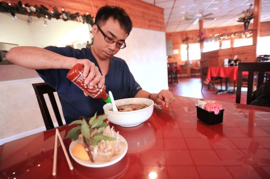 Ricky Phan pours on the heat and flavor before eating Pho Tai soup at Pho Four Seasons Vietnamese Cuisine. Guiseppe Barranco/The Enterprise Photo: Guiseppe Barranco/The Enterprise