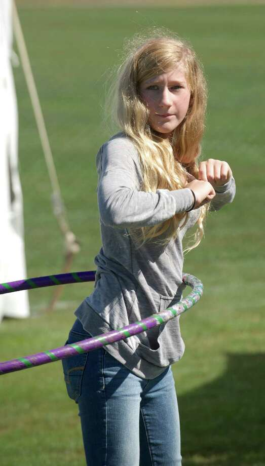 Kaia Burr, 13, of Trumbull, keeps a hoop from Velvet Orchid Hoops spinning during the Newtown Arts Festival 2014, held at the Fairfield Hill Campus, in Newtown, Conn, on Sunday, September 14, 2014. Photo: H John Voorhees III / The News-Times Freelance