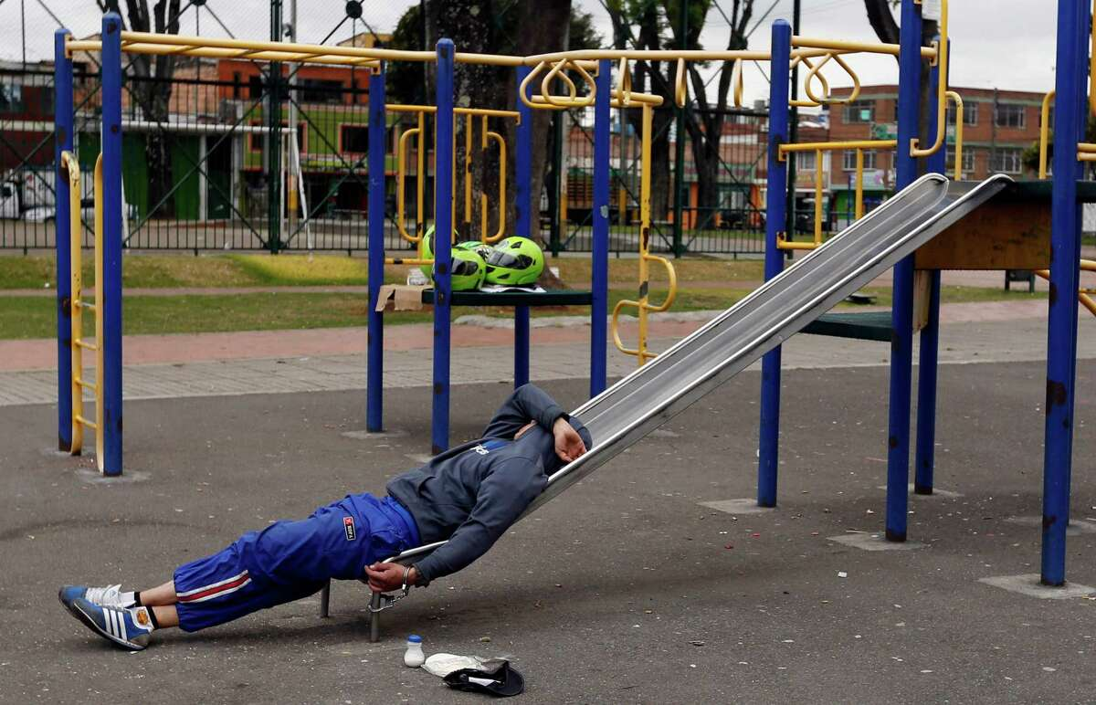 A detainee rests, handcuffed to a slide, at a children's playground in a public park in Bogota, Colombia, Thursday, Sept. 11, 2014. Due to overcrowding at a detention center located across the street, the park has been converted into makeshift holding area, where detainees, most accused of petty crimes, are kept for days waiting for a prosecutor's decision.