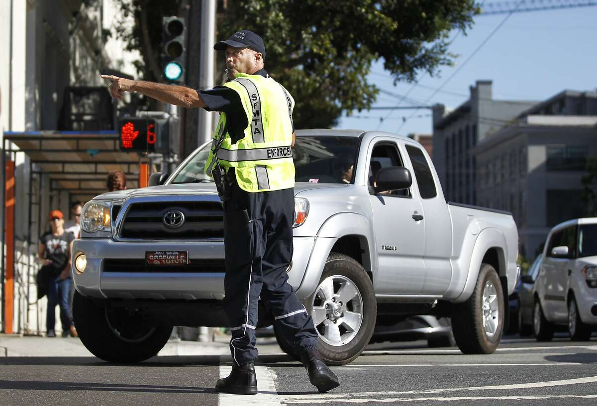 SFMTA officer only identified for safety reasons as badge number 73, directs traffic at 2nd and Bryant Streets as part of San Francisco Municipal Transportation Agency's (SFMTA) testing of