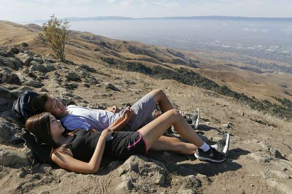 Alec Deng, of Palo Alto and Carolyn Do, of San Jose are rewarded with a spectacular view after hiking to the top of Mission Peak above Fremont , Calif., on Saturday Sept. 13, 2014. Crowds of hikers can be found climbing the steep grade up to the summit of East Bay Regional Park's Mission Peak, at the top they find a strange post embedded into an outcropping of rocks.