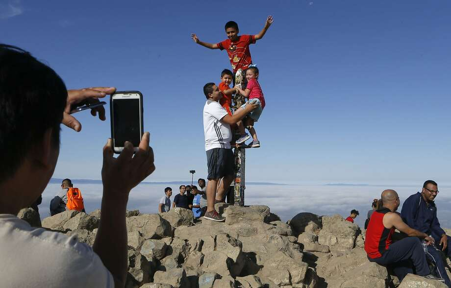Moises Tapi takes a photograph of Alejandro Cruz with three children on the summit post atop Mission Peak in Fremont. Photo: Michael Macor, The Chronicle