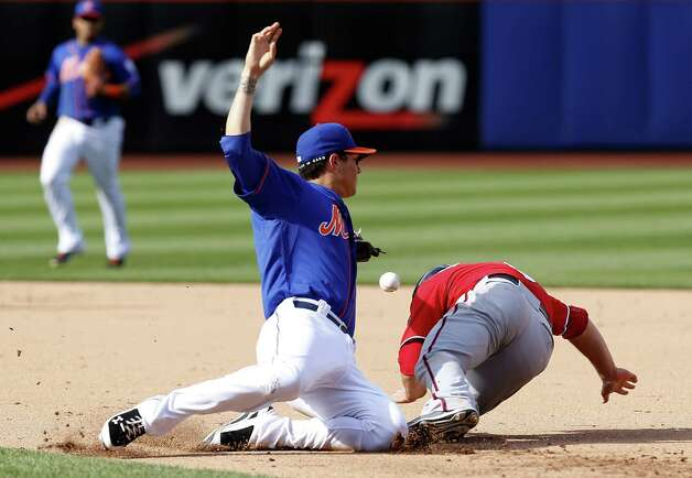 New York Mets second baseman Wilmer Flores, left, loses the ball while trying to tag Washington Nationals' Danny Espinosa during the ninth inning of the baseball game at Citi Field, Sunday, Sept. 14, 2014 in New York. A run scored on the error and the Nationals defeated the Mets 3-0. (AP Photo/Seth Wenig) ORG XMIT: NYSW109 Photo: Seth Wenig / AP