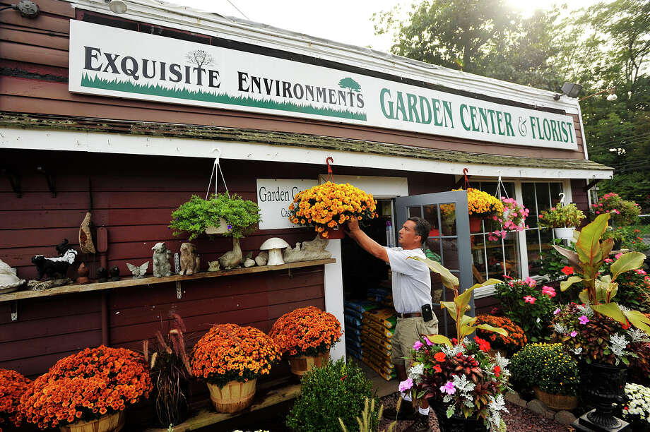 Owner Kyle Wells prunes a flower near the doorway to his business, Exquisite Environments, in Stamford, Conn., on Sunday, Sept. 14, 2014. Photo: Jason Rearick / Stamford Advocate
