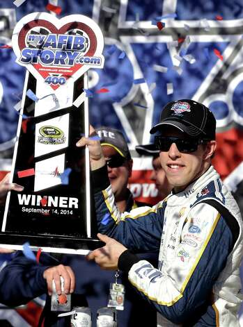 Brad Keselowski holds up the trophy in Victory Lane after winning the NASCAR Sprint Cup series auto race at Chicagoland Speedway in Joliet, Ill., Sunday, Sept. 14, 2014. (AP Photo/Nam Y. Huh) ORG XMIT: ILNH122 Photo: Nam Y. Huh / AP