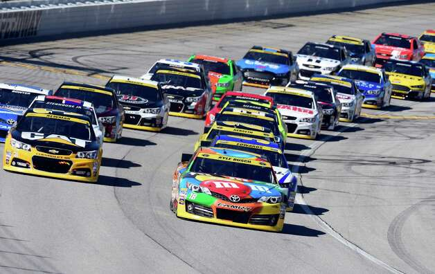 Kyle Busch (18) leads the field at the start of the NASCAR Sprint Cup series auto race at Chicagoland Speedway in Joliet, Ill., Sunday, Sept. 14, 2014. (AP Photo/Paul J. Bergstrom) ORG XMIT: ILNH109 Photo: Paul J. Bergstrom / FRE171230AP