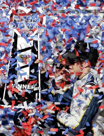 Brad Keselowski (2) looks at the trophy as he celebrates with his crew in Victory Lane after winning the NASCAR Sprint Cup series auto race at Chicagoland Speedway in Joliet, Ill., Sunday, Sept. 14, 2014. (AP Photo/Nam Y. Huh)  ORG XMIT: ILNH123 Photo: Nam Y. Huh / AP