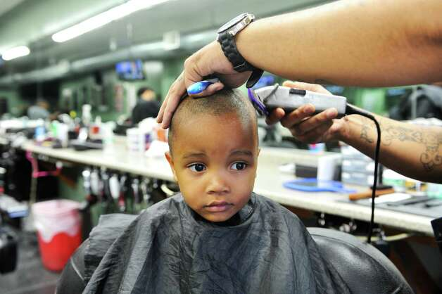 Aiden Kershaw, 3, of Albany gets his hair cut by Khamen Monger, a barber at Brick's Barber Salon during the eighth annual Community Cuts on Sunday, Sept. 14, 2014, in Albany, N.Y. The event is sponsored by Brick's, the George Biddle Kelley Education Foundation, New York State United Teachers, National Pan-Hellenic Council and Jay Allen Barber Studio. Organizers said they expect to do 500 free haircuts for children. Along with haircuts children taking part in the event were given backpacks with school supplies and books.  Other groups also involved in the event were, the Albany, N.Y. chapters of Alpha Phi Alpha Fraternity, Kappa Alpha Psi Fraternity, Omega Psi Phi Fraternity, Phi Beta Sigma Fraternity, Iota Phi Theta Fraternity, Capital District NPHC, and 100 Black Men.  (Paul Buckowski / Times Union) Photo: Paul Buckowski / 00028602A