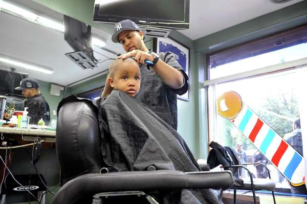Khamen Monger, a barber at Brick's Barber Salon gives a free haircut to Aiden Kershaw, 3, of Albany during the eighth annual Community Cuts on Sunday, Sept. 14, 2014, in Albany, N.Y. The event is sponsored by Brick's, the George Biddle Kelley Education Foundation, New York State United Teachers, National Pan-Hellenic Council and Jay Allen Barber Studio. Organizers said they expect to do 500 free haircuts for children. Along with haircuts children taking part in the event were given backpacks with school supplies and books.  Other groups also involved in the event were, the Albany, N.Y. chapters of Alpha Phi Alpha Fraternity, Kappa Alpha Psi Fraternity, Omega Psi Phi Fraternity, Phi Beta Sigma Fraternity, Iota Phi Theta Fraternity, Capital District NPHC, and 100 Black Men.  (Paul Buckowski / Times Union) Photo: Paul Buckowski / 00028602A