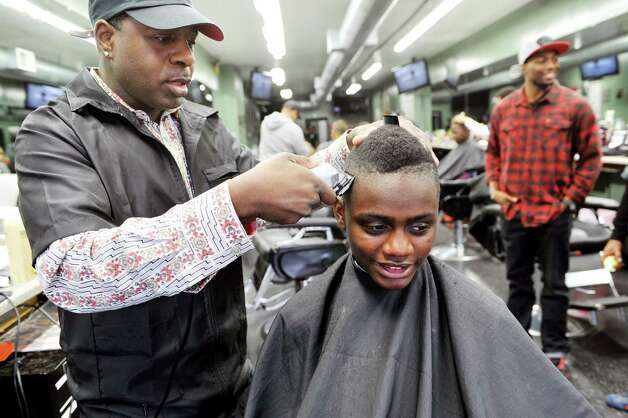 Jason Ellis, left, one of the co-owners of Brick's Barber Salon, gives a haircut to Ryan Abdul-Malik, 14, a Columbia High School student at Brick's Barber Salon during the eighth annual Community Cuts on Sunday, Sept. 14, 2014, in Albany, N.Y. The event is sponsored by Brick's, the George Biddle Kelley Education Foundation, New York State United Teachers, National Pan-Hellenic Council and Jay Allen Barber Studio. Organizers said they expect to do 500 free haircuts for children. Along with haircuts children taking part in the event were given backpacks with school supplies and books.  Other groups also involved in the event were, the Albany, N.Y. chapters of Alpha Phi Alpha Fraternity, Kappa Alpha Psi Fraternity, Omega Psi Phi Fraternity, Phi Beta Sigma Fraternity, Iota Phi Theta Fraternity, Capital District NPHC, and 100 Black Men.  (Paul Buckowski / Times Union) Photo: Paul Buckowski / 00028602A