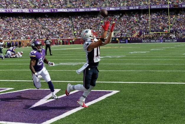 New England Patriots wide receiver Julian Edelman, right, catches a 9-yard touchdown pass as Minnesota Vikings cornerback Captain Munnerlyn watches during the second quarter of an NFL football game Sunday, Sept. 14, 2014, in Minneapolis. (AP Photo/Jim Mone) ORG XMIT: MNJR119 Photo: Jim Mone / AP