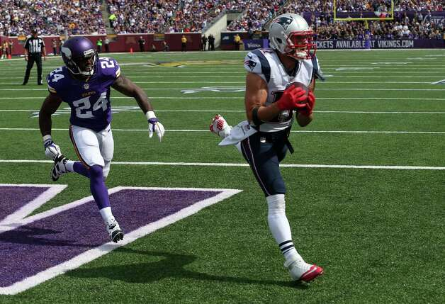 New England Patriots wide receiver Julian Edelman, right, catches a 9-yard touchdown pass as Minnesota Vikings cornerback Captain Munnerlyn watches during the second quarter of an NFL football game Sunday, Sept. 14, 2014, in Minneapolis. (AP Photo/Jim Mone) ORG XMIT: MNJR120 Photo: Jim Mone / AP