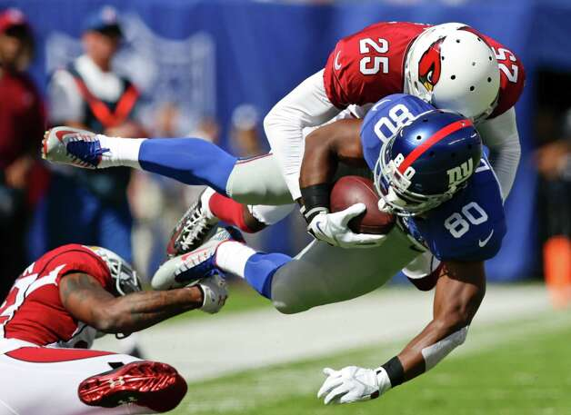 Arizona Cardinals cornerback Jerraud Powers (25) tackles New York Giants wide receiver Victor Cruz (80) during the first half of an NFL football game Sunday, Sept. 14, 2014, in East Rutherford, N.J.  (AP Photo/Kathy Willens) ORG XMIT: ERU117 Photo: Kathy Willens / AP