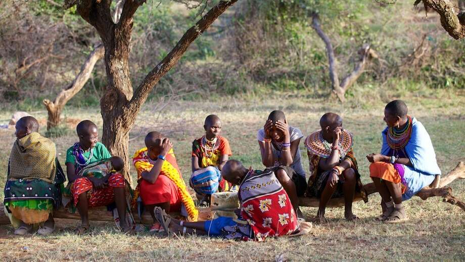Women from the Ewaso community in Kenya, Africa relax on a tree branch. (James Towne) / The Duncan Group, Inc.
