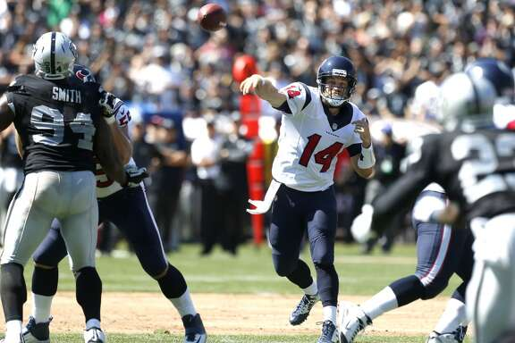 Houston Texans quarterback Ryan Fitzpatrick (14) throws a pass over Oakland Raiders defensive tackle Antonio Smith (94) during the first quarter of an NFL football game at O.co Coliseum on Sunday, Sept. 14, 2014, in Oakland, Calif. ( Brett Coomer / Houston Chronicle )