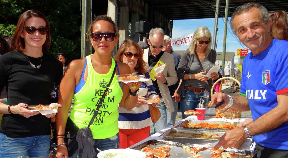 Erin Coakley and Jamie Tran try pizza and ziti from Tony Funicello of Tutti's Ristorante at the Slice of Saugatuck Festival on Sunday. Photo: Mike Lauterborn / Westport News