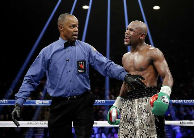 Floyd Mayweather speaks to referee Kenny Bayless, left, after he claimed that Marcos Maidana bit his hand during their WBA welterweight and WBC super  welterweight title fight, Saturday, Sept. 13, 2014, in Las Vegas. (AP Photo/John Locher) ORG XMIT: NVSM151 Photo: John Locher / AP