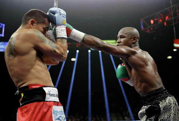 Floyd Mayweather punches Marcos Maidana, left, during their WBA welterweight and WBC super  welterweight title fight, Saturday, Sept. 13, 2014, in Las Vegas. (AP Photo/John Locher) ORG XMIT: NVSM144 Photo: John Locher / AP