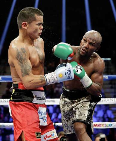 Floyd Mayweather, right, follows through on a punch at Marcos Maidana during their title boxing match Saturday, Sept. 13, 2014, in Las Vegas. (AP Photo/John Locher) ORG XMIT: NVSM166 Photo: John Locher / AP