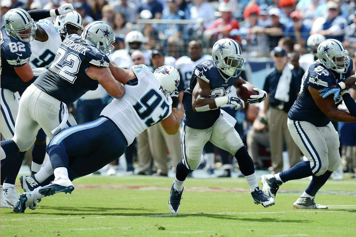 Dallas Cowboys running back Joseph Randle (21) carries the ball as center Travis Frederick (72) blocks Tennessee Titans defensive tackle Mike Martin (93) in the first quarter of an NFL football game Sunday, Sept. 14, 2014, in Nashville, Tenn.
