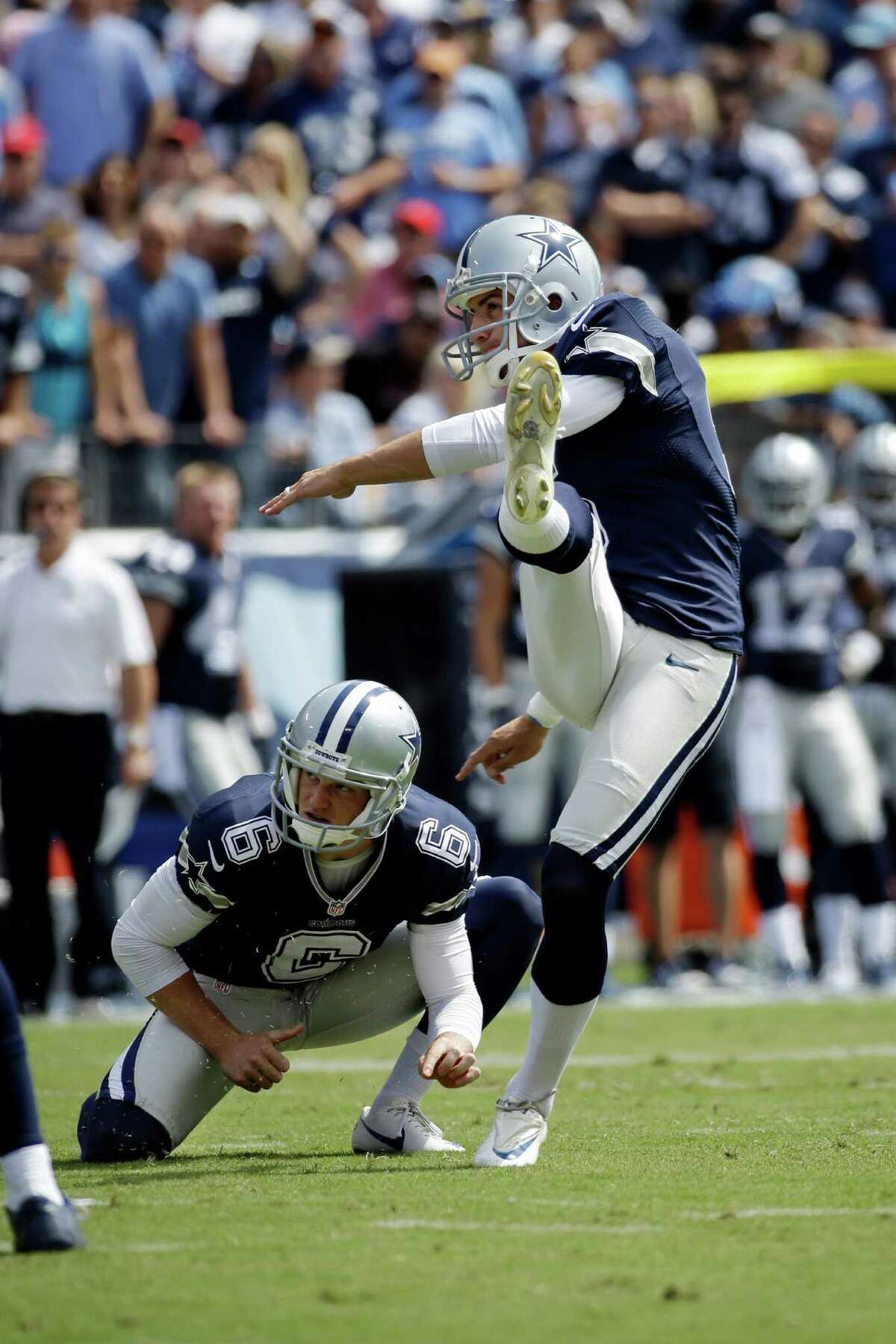 Dallas Cowboys kicker Dan Bailey right, kicks a field goal against the Tennessee Titans as Chris Jones (6) holds in the first quarter of an NFL football game Sunday, Sept. 14, 2014, in Nashville, Tenn.