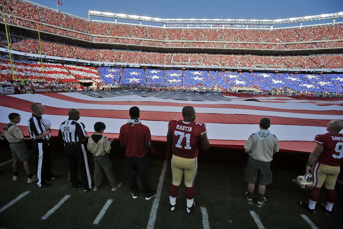 Jonathan Martin (71) holds the pregame flag with Boy Scouts before the 49ers played the Chicago Bears at Levi's Stadium in Santa Clara on Sunday, September 14, 2014.