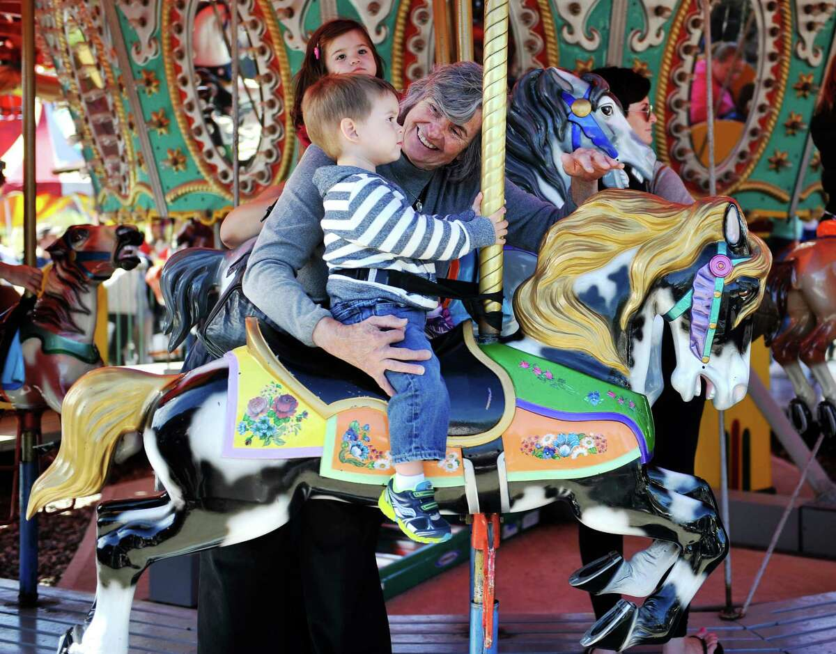 Gloria Knorr of Colonie rides the merry-go-round with her grandson, Nicholas Bolling, 2, of Cohoes during the final day of business at Hoffman's Playland, on Sunday, Sept. 14, 2014, in Latham, N.Y. Knorr often came to Hoffman's when she was a child. The business first opened in 1952. (Paul Buckowski / Times Union)