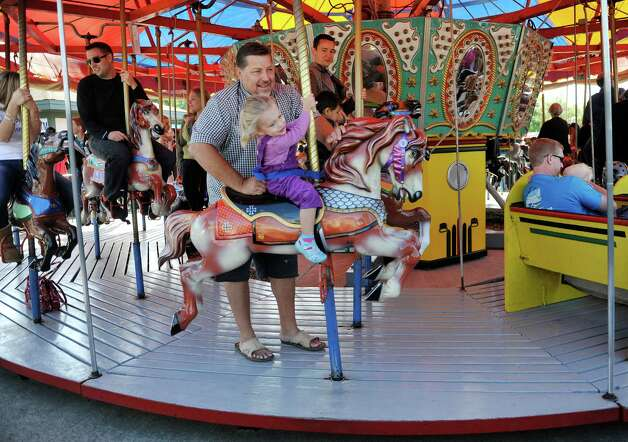 Walt Weglinski from Alplaus rides the merry-go-round with his daughter, Karina, 3,  during the final day of business at Hoffman's Playland, on Sunday, Sept. 14, 2014, in Latham, N.Y.  The business first opened in 1952.  (Paul Buckowski / Times Union) Photo: Paul Buckowski / 00028503A