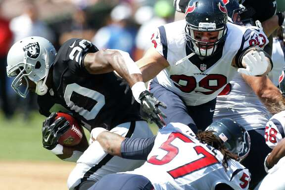 A swarming Texans defense led by inside linebacker Justin Tuggle (57) and defensive end J.J. Watt (99) stops Raiders running back Darren McFadden at the line of scrimmage. The Raiders rushed for only 101 yards.