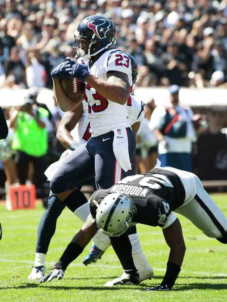 Arian Foster puts the Texans ahead by two touchdowns in the first quarter by easing past Raiders safety Charles Woodson on a 5-yard scoring run. Photo: Brett Coomer, Staff / © 2014  Houston Chronicle