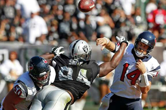 Ryan Fitzpatrick stands tall in the pocket, taking a hit from Raiders defensive tackle Antonio Smith while delivering a pass during the third quarter. Fitzpatrick completed 14 of 19 passes while compiling a 129.1 quarterback rating that was the second highest of his career.