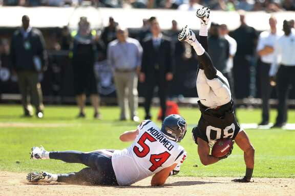 Texans linebacker Mike Mohamed (54) upends Raiders wide receiver Rod Streater (80) in the second quarter of Sunday's game.