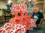 """Dan Suttin, a SAC math tutor, kneels in his """"Spartan but spacious"""" studio beside """"Mini-Me Mega-Tetra,"""" a structure based on the diamond lattice, in the Octa-Tetra Museum at 1100 Broadway. He has set up partnerships with area educators and won a $1,000 AwesomeSA grant."""