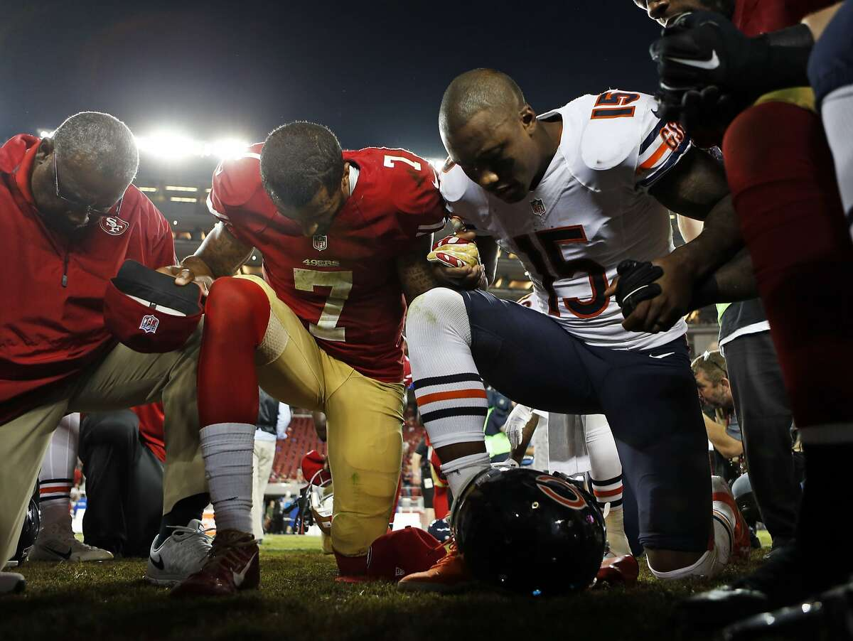 In this file photo, San Francisco 49ers' Colin Kaepernick prays with Chicago Bears' Brandon Marshall after Bears' 28-20 win during NFL game at Levi's Stadium in Santa Clara, Calif. on Sunday, September 14, 2014.