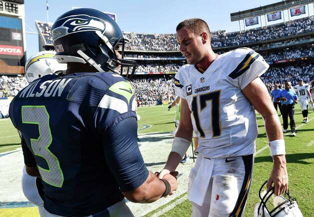 San Diego Chargers quarterback Philip Rivers (17), right, shakes hands with Seattle Seahawks quarterback Russell Wilson (3) after the Chargers defeated the Seahawks 30-21 in an NFL football game Sunday, Sept. 14, 2014, in San Diego. (AP Photo/Denis Poroy) ORG XMIT: CADP102 Photo: DENIS POROY / FR59680 AP