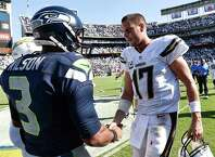 San Diego Chargers quarterback Philip Rivers (17), right, shakes hands with Seattle Seahawks quarterback Russell Wilson (3) after the Chargers defeated the Seahawks 30-21 in an NFL football game Sunday, Sept. 14, 2014, in San Diego. (AP Photo/Denis Poroy) ORG XMIT: CADP102