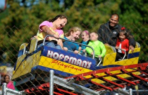 Cousins, Madison Campbell, left, 12, from Troy and Katie Carney, 8, from Stillwater ride the roller coaster during the final day of business at Hoffman's Playland, on Sunday, Sept. 14, 2014, in Latham, N.Y. The business first opened in 1952. (Paul Buckowski / Times Union)