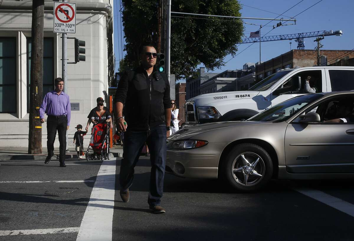 Pedestrians walk around cars blocking a crosswalk as SFMTA workers keep count of how many cars do so at 2nd and Bryant streets as part of San Francisco Municipal Transportation Agency's (SFMTA) testing of