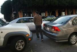 A pedestrian walks between cars blocking a crosswalk at 2nd and Bryant streets in San Francisco.