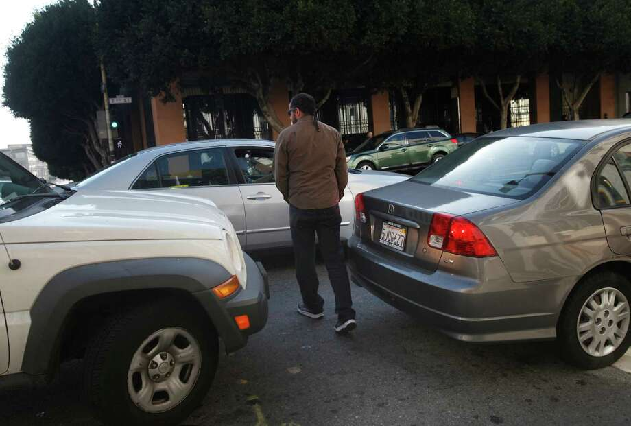 A pedestrian walks between cars blocking a crosswalk at 2nd and Bryant streets in San Francisco. Photo: Leah Millis / The Chronicle / ONLINE_YES
