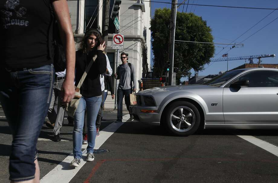 "Pedestrians walk around a car blocking a crosswalk as SFMTA workers keep count of how many cars do so at 2nd and Bryant streets as part of San Francisco Municipal Transportation Agency's (SFMTA) testing of ""Don't Block the Box"" enforcement program at two SOMA intersections Sept. 11, 2014 in San Francisco, Calif. The program is meant to stop people from blocking intersections with their cars during heavy traffic times, such as during Giants games. Photo: Leah Millis, The Chronicle"