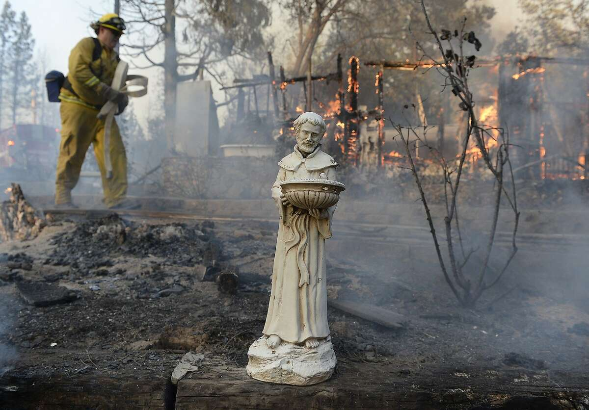 A religious statue is almost all that is left from a home that burned to the ground on Cedar Drive in Oakhurst, Calif., Sunday, Sept. 14, 2014, as two raging wildfires in the state forced hundreds of people to evacuate their homes. The California Department of Forestry and Fire Protection said flames damaged or destroyed at least 21 structures. (AP Photo/The Fresno Bee, Mark Crosse)