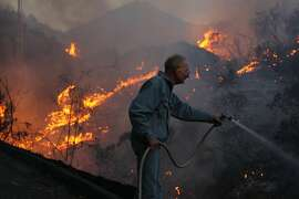 "James Harkins, 72, refused to evacuate his home of more than 20 years in San Marcos, Ca., and uses a garden hose to combat the flames racing up the hillside toward his home, Thursday, May 16, 2014. ""Let it go up in smoke,"" he quipped. ""No, no, no. Not without a fight."" Harkins welcomed the help of some firefighters who came to aid him. ""What about my things, my memories, my things to pass on, he added. ""It's mine. If it burns down I don't have a lot left."" (Rick Loomis/Los Angeles Times/MCT)"