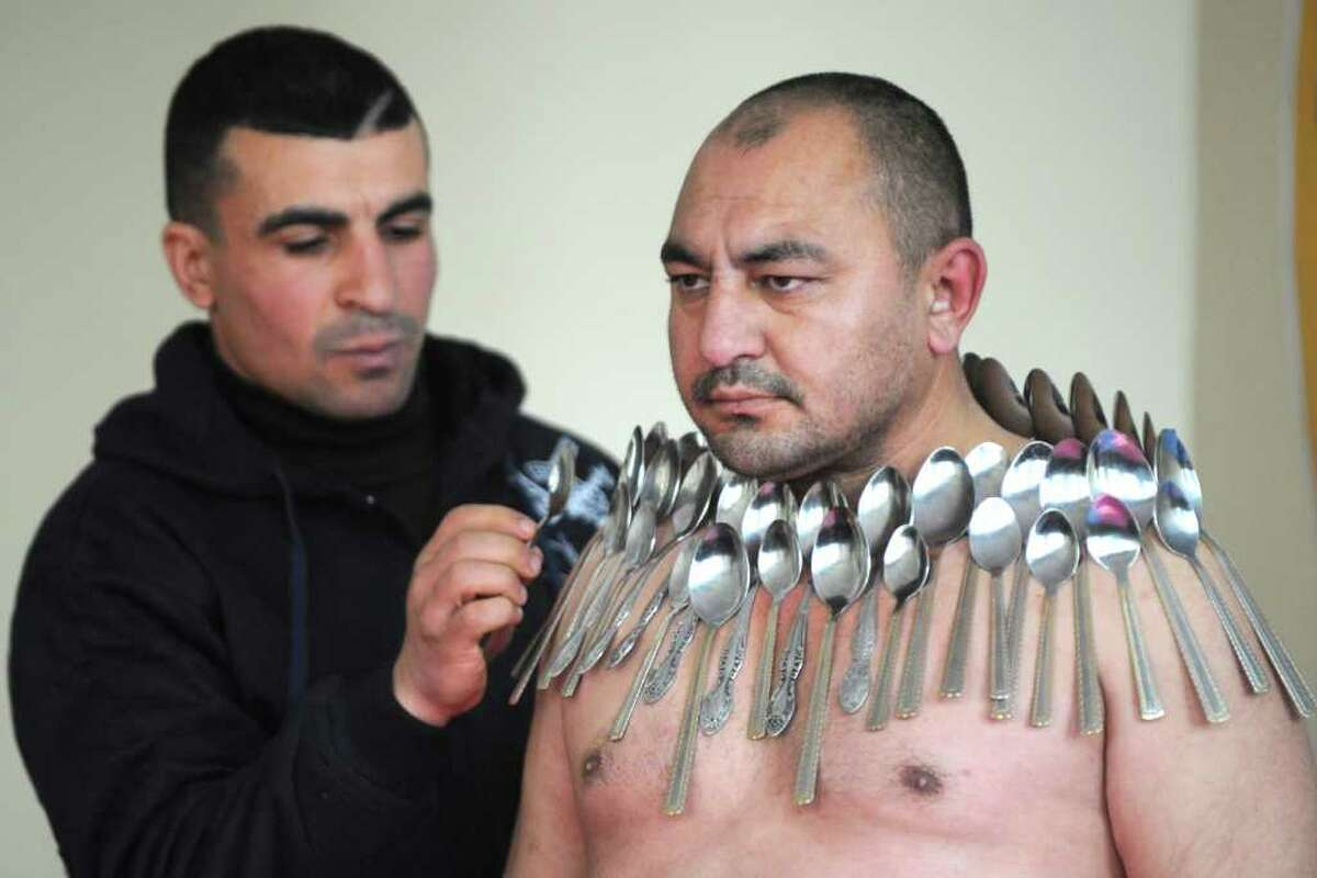 Etibar Elchiyev (R) poses with 50 metal spoons stuck to his body during an attempt to break the Guinness World Record for
